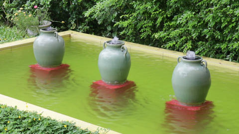 Ceramic water-filled jars decorated in outdoors garden Live Action