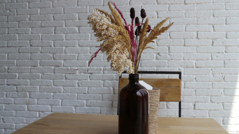 Dried flowers in vase at white coffee shop with table and chair Live Action