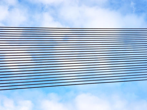 Black metal line rows against a blue sky with white clouds. Background of フォト