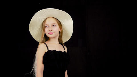 Young girl in black dress and a hat Footage