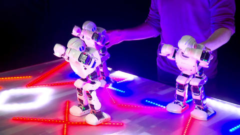 Robots dance, man controls robots, dance moves, glowing dance floor Live Action
