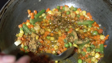 The chef adds spicy flavored spices to the pan with the frozen vegetable mixture Live Action