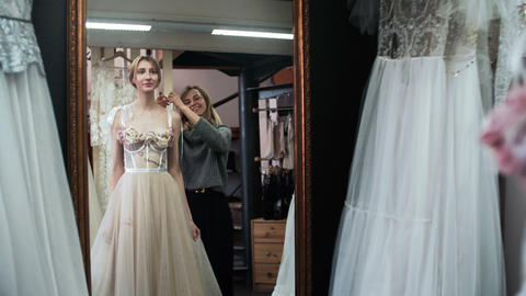 Fashion Tailor is helping bride choose wedding dress. Wedding Gown Fitting Footage