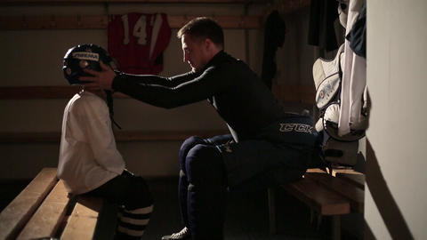 Dad and son hockey player dress up in the locker room 24 of 42 Live Action