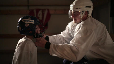 Dad and son hockey player dress up in the locker room 27 of 42 Live Action