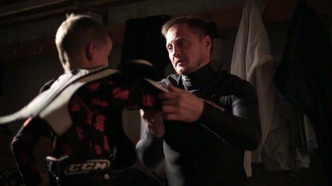 Dad and son hockey player dress up in the locker room 04 of 42 Live Action