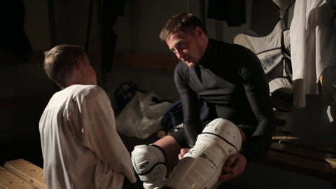 Dad and son hockey player dress up in the locker room 11 of 42 Live Action