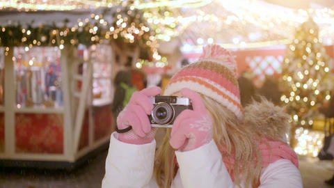 Young blond smiling female in warm clothes with retro film camera shooting a Footage