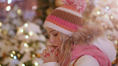 Cute woman feeling cold and warming her hands in winter evening Footage