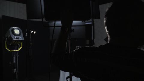 Lighting engineer on the set adjusts the brightness of the spotlight Footage