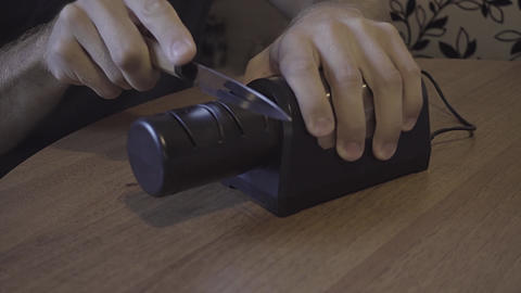 Sharpening a kitchen knife with an electronic sharpener Footage