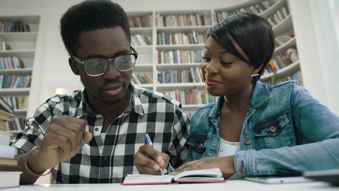 African students making some note in the note book in library Footage