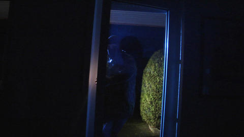 burglar comes in watch around with torch 10843 Stock Video Footage