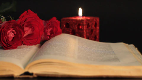 book, candle and red roses Stock Video Footage