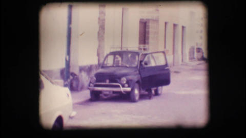 Vintage 8mm. Man getting into his car Stock Video Footage