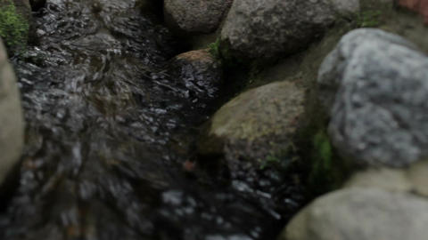 The water flows among the stones in the city park Stock Video Footage