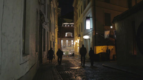 Street of the old city at night. The silhouettes of passers-by Footage