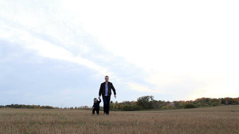 Young father with his son walking in the field Footage