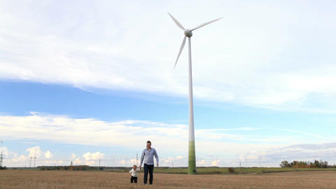 Father and son walking near the wind turbine Footage