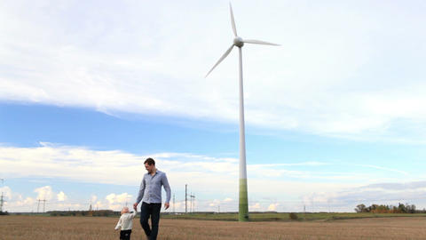 Father and son walking near the wind turbine Stock Video Footage