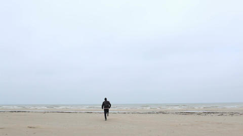 A young man is running to the sea Stock Video Footage