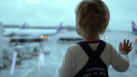 A little boy looks at the planes at the airport. Shallow... Stock Video Footage