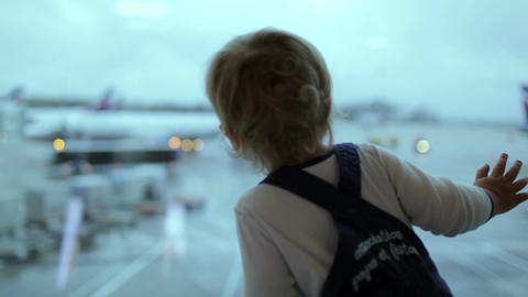 A little boy looks at the planes at the airport. Shallow dof, blinking lights Footage