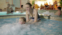 Young mother is playing with her son in the pool of the... Stock Video Footage