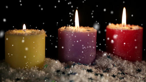 Candles isolated on black. Snow is falling. Holiday background with copyspace for text Footage