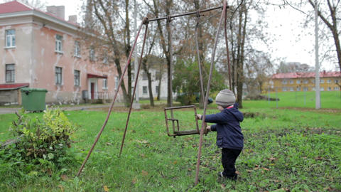 The little boy is swinging an old swing. Johvi, Estonia Stock Video Footage