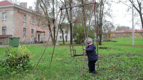 The little boy is swinging an old swing. Johvi, Estonia Footage