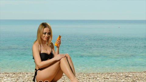 Girl blonde in swimsuit posing near the sea and rubs sunblock Footage