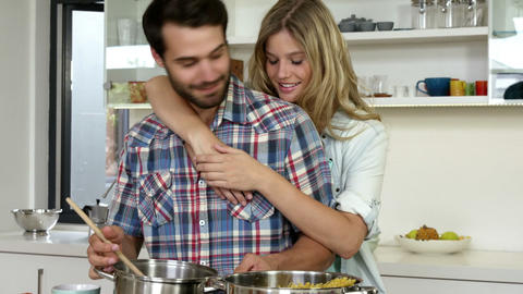Cute girl hugging his boyfriend while he is cooking Live Action