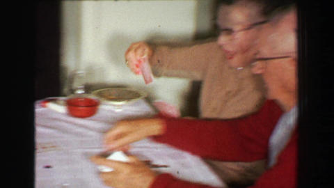 1957: Family playing poker cards after Thanksgiving dinner at kitchen table Footage