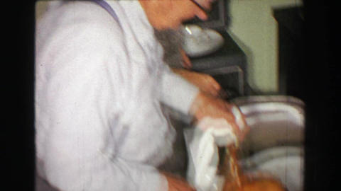 1957: Mother bringing out Thanksgiving turkey dinner father carving bird Footage