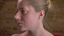 Closeup portrait of young caucasian female turning from side to side revealing Footage