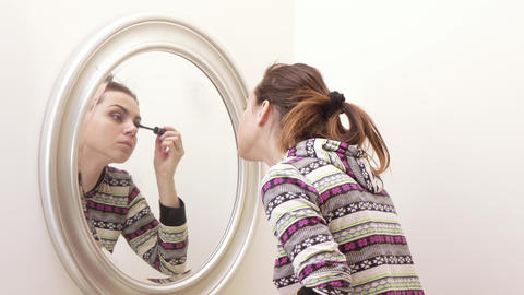 Girl paints face at mirror Live Action