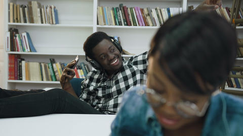 African male student using smart phone while another…, Live Action