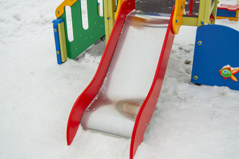 Empty metal slide for small children on snow-covered Playground, white snow Fotografía