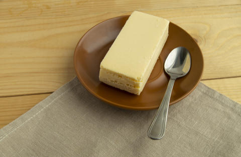 A piece of classic vanilla new York cheesecake on a light wooden background and Photo