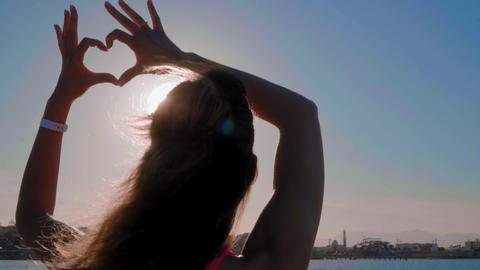The girl make heart with her hands over sea background. Silhouette hand in heart Footage