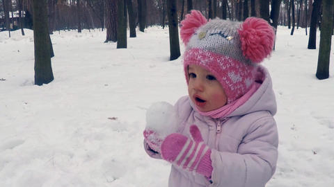 A little girl in a red hat with big bamboos eats a snowball in the winter forest Footage