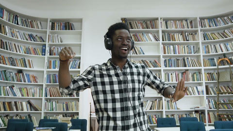 Portrait shot of young african male student dancing in the modern library while Live Action