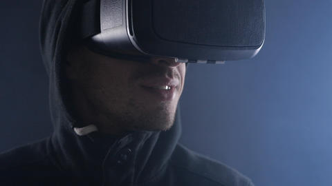 Close up Young man in hood using virtual reality headset on black smoky Live Action