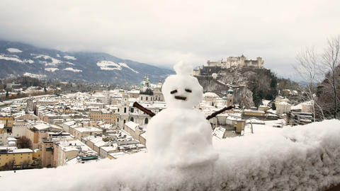 snowman with background the snow-capped Salzburg fortress Footage