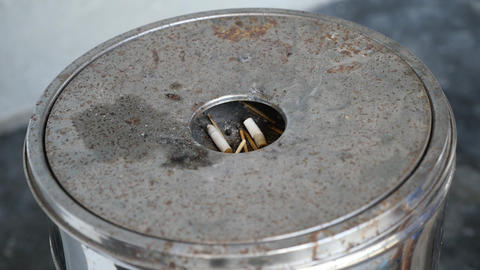 Detail of Male hand Stubbing Out Cigarette in sand ashtray bin Live Action