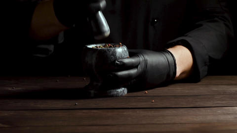 Chef in black latex gloves holds a stone mortar with a mixture of peppers, Archivo