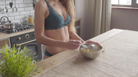 Young woman in lingerie with a perfect belly stiring a whisk in a large bowl Footage