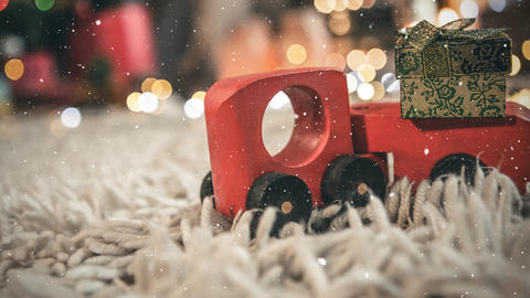 Red toy car on a carpet in a living room decorated for christmas combined with falling snow Animation