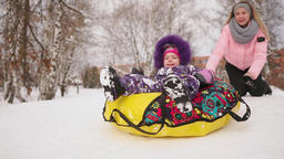 Happy mom and daughter sledding in winter in snow and playing snowballs. mother Footage